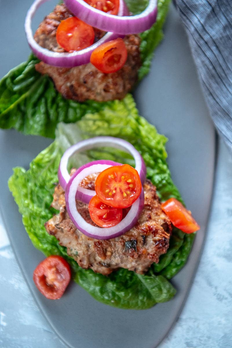 turkey burger patty on lettuce topped with tomatoes and red onion slices