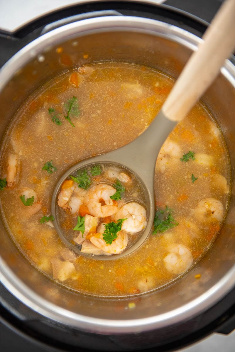 ladle full of shrimp and broth in instant pot
