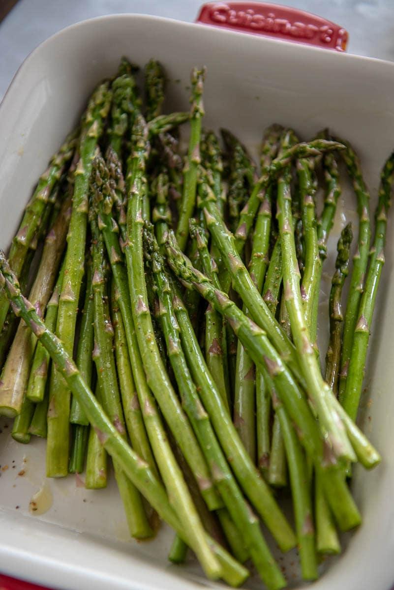 raw asparagus in a white dish