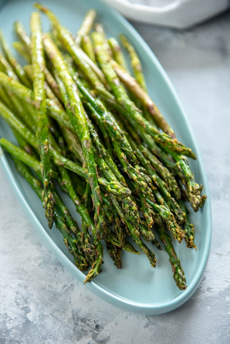 cooked asparagus in a white serving dish