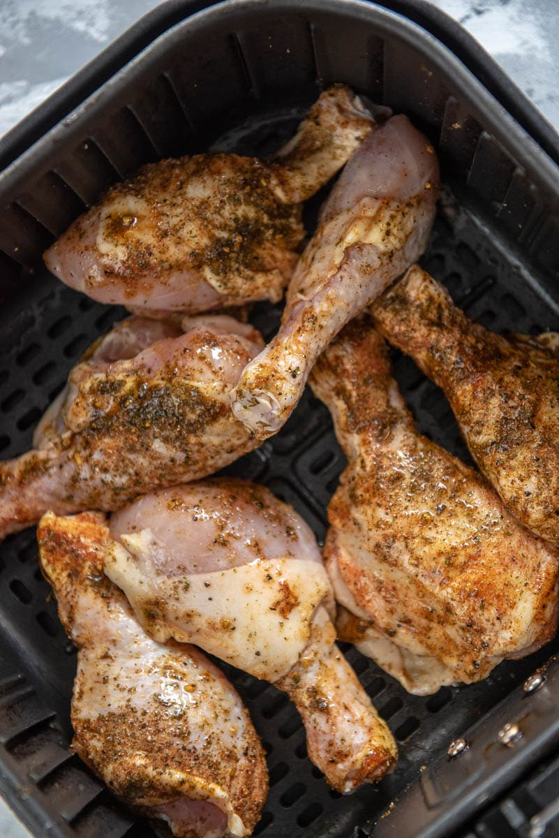seasoned chicken legs ready to cook in air fryer basket