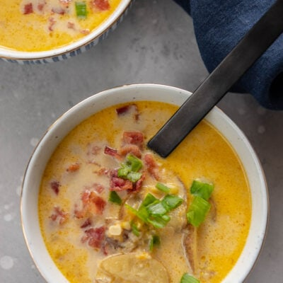 two blue and white bowls filled with corn chowder topped with crumbled bacon and green onions