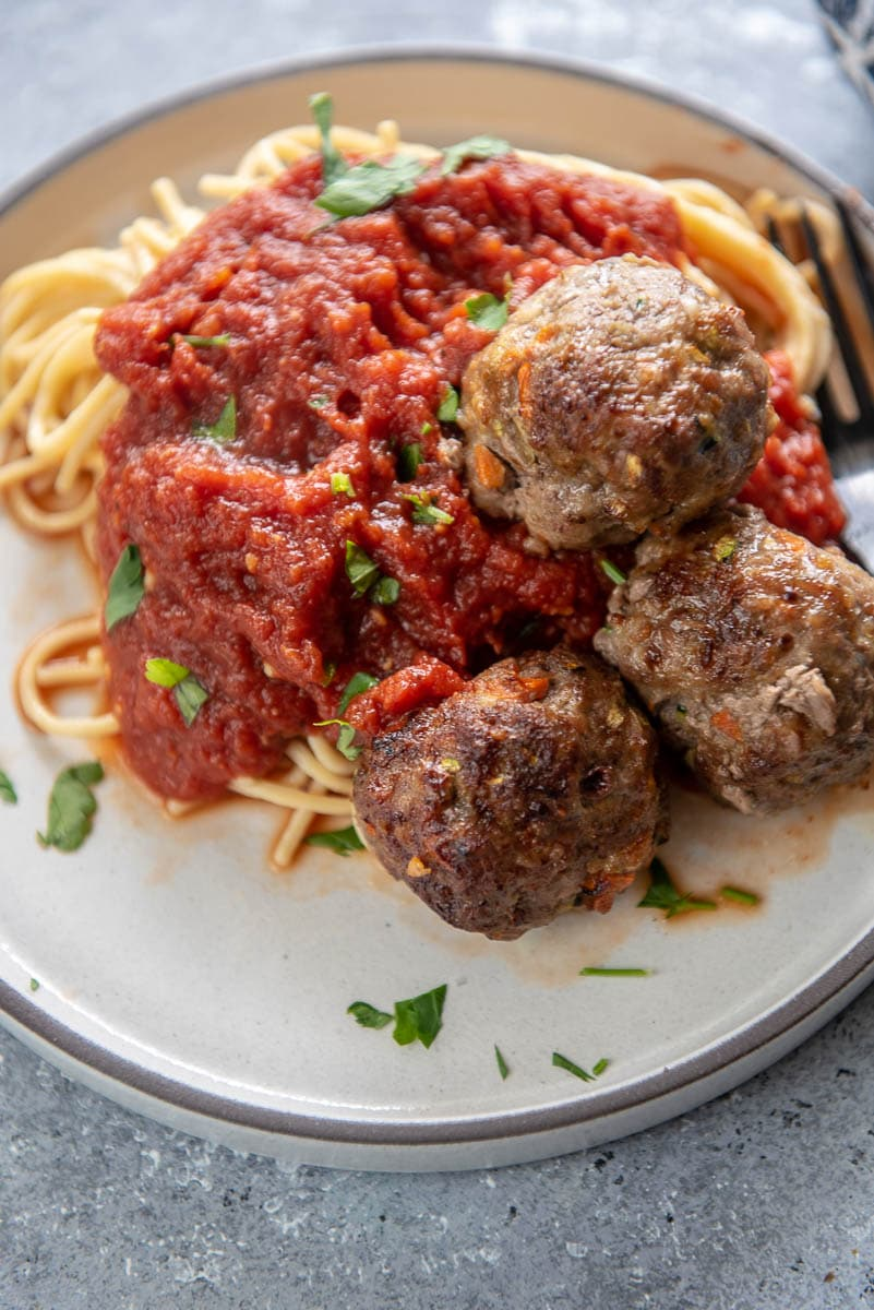 3 meatballs over spaghetti noodles with red sauce on white plate