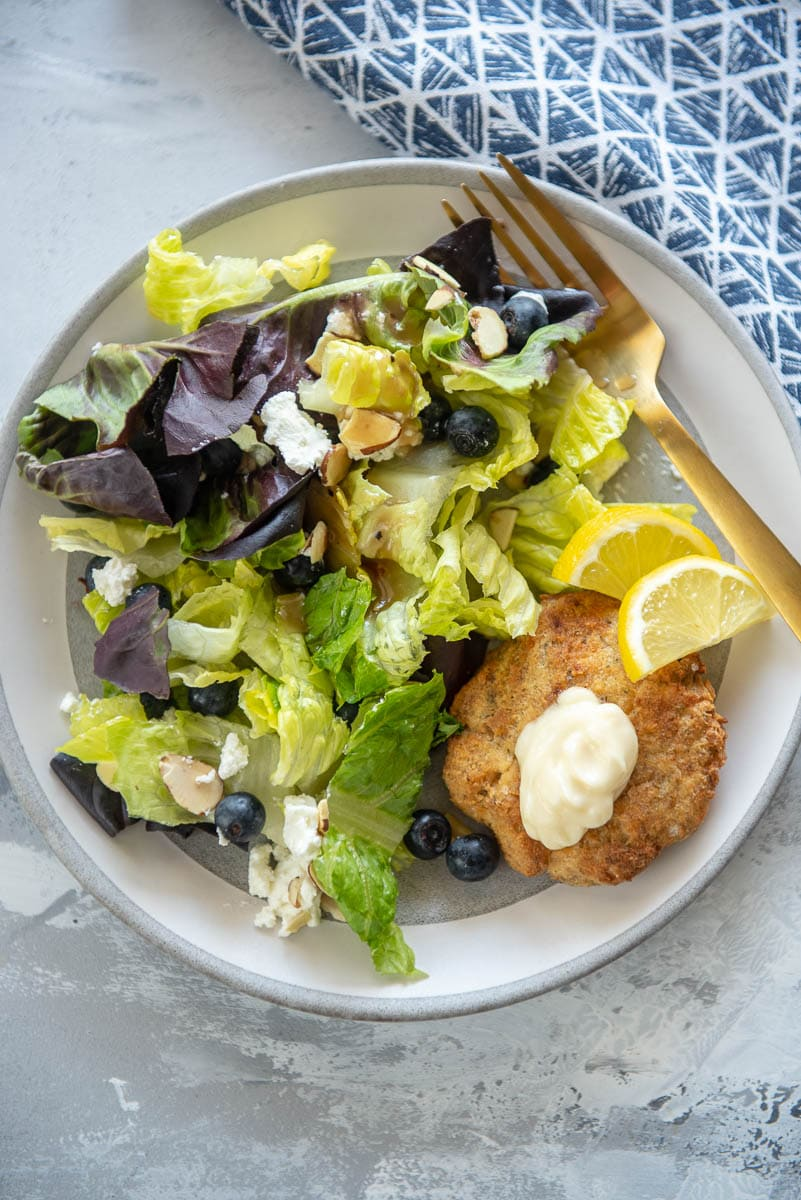 salmon patties and green salad on white plate