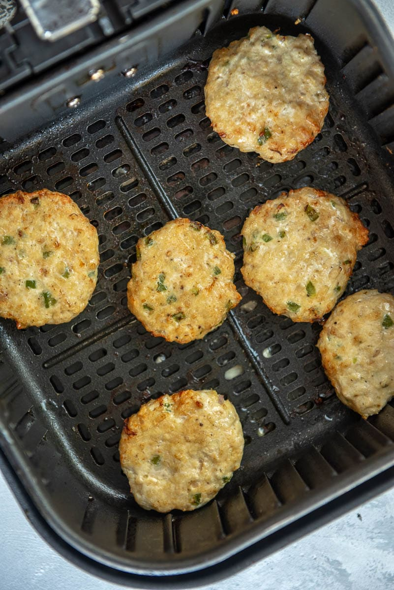 6 cooked chicken sausage patties in air fryer basket