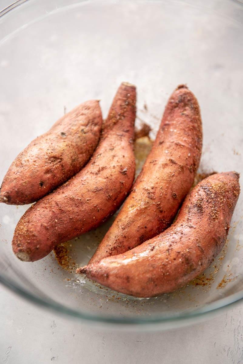 seasoned sweet potatoes in a glass bowl