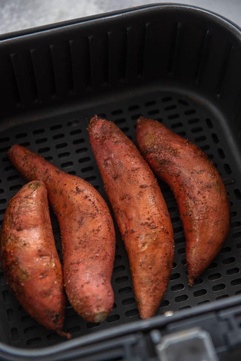 4 seasoned sweet potatoes in an air fryer basket