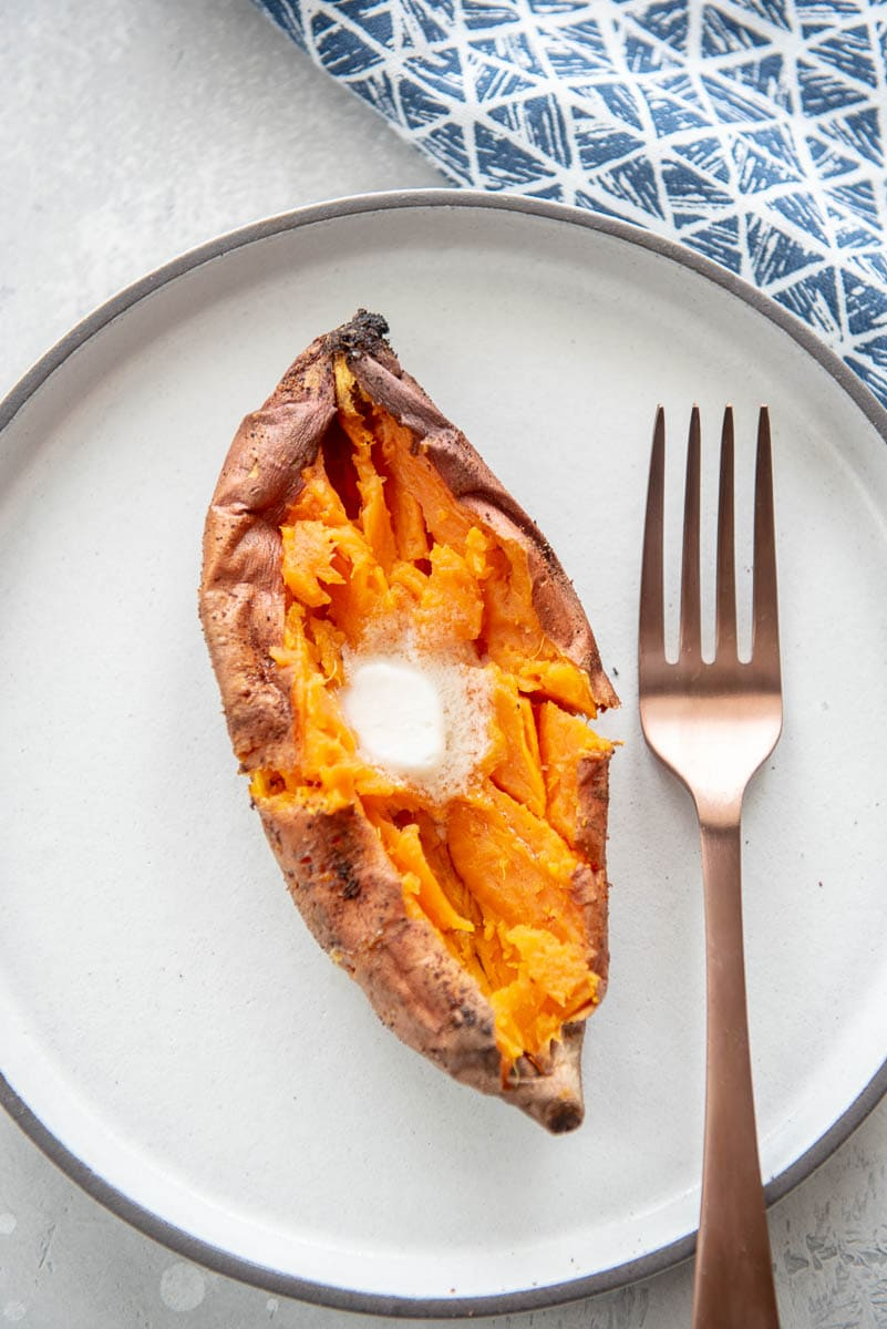 overhead view of baked sweet potato cut in half and topped with butter on white plate