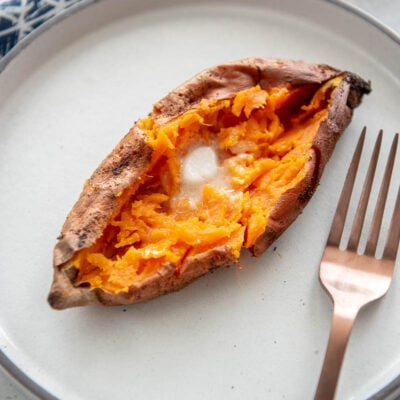 split open baked sweet potato topped with butter on a white plate