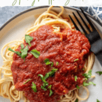 spaghetti and sauce on white plate with fork