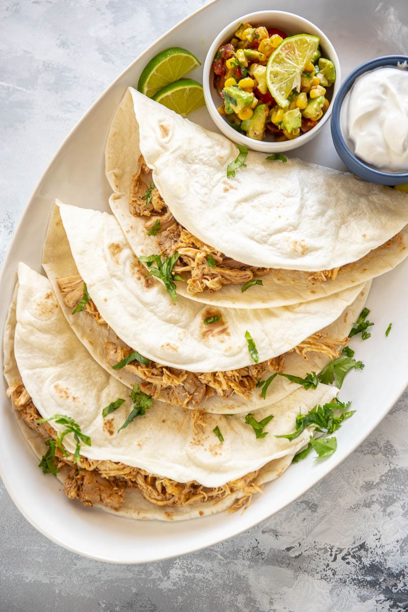 3 chicken tacos wit flour shells on a white platter with a bowl of corn salsa