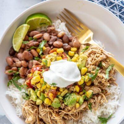 burrito bowl in a white bowl with lime and sour cream
