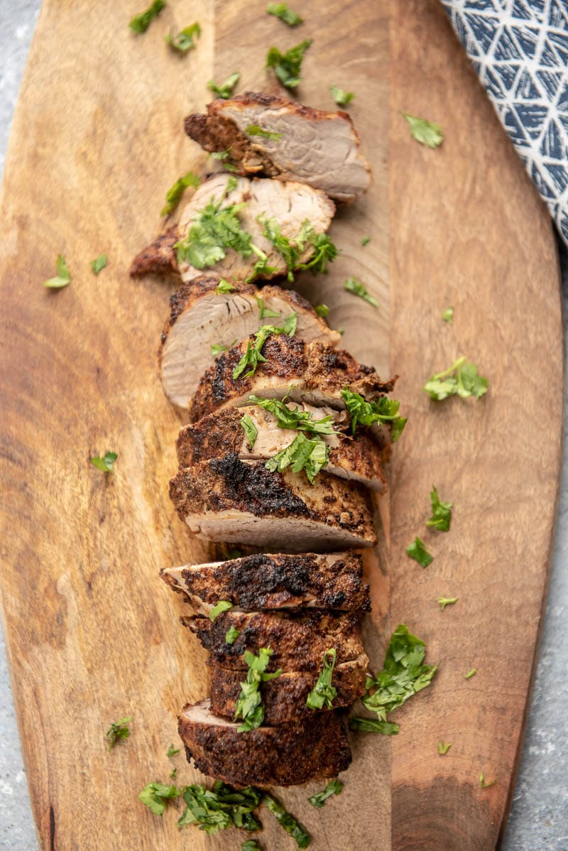 cooked pork tenderloin on a wood plank with herb garnish