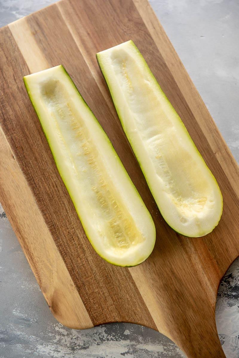 two zucchini halves on a cutting board