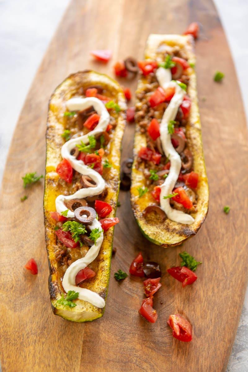 taco stuffed zucchini boats on a cutting board