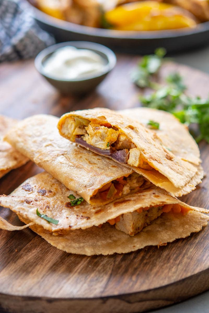 chicken fajita quesadillas on a wooden plank with dressing
