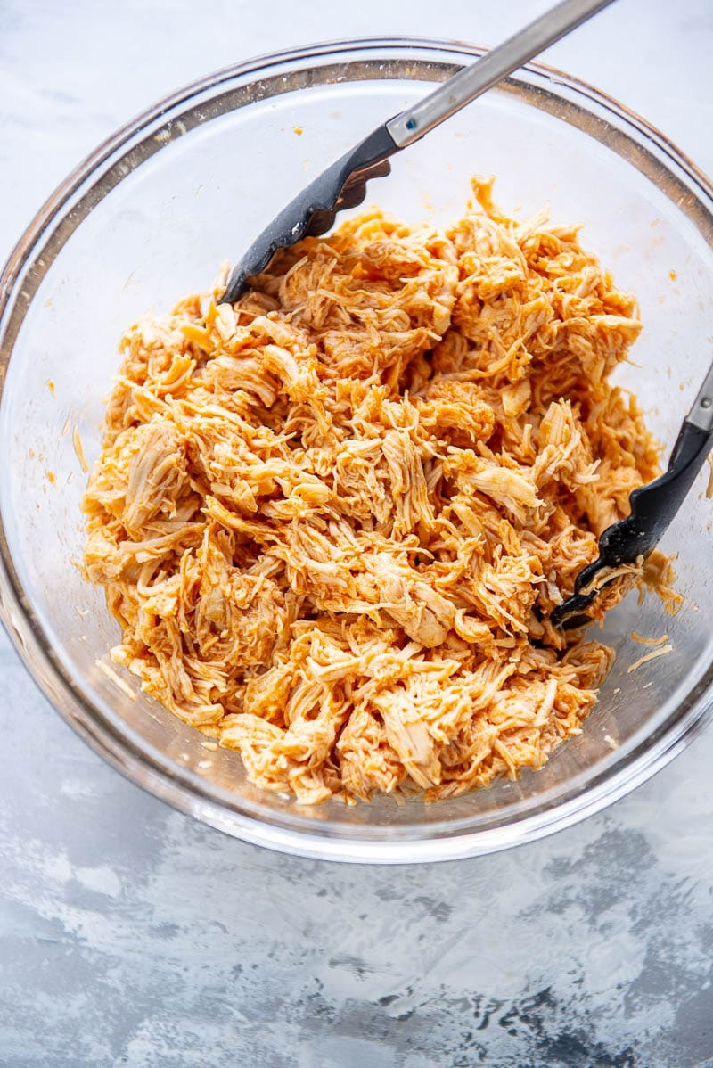shredded buffalo chicken in a glass bowl with tongs