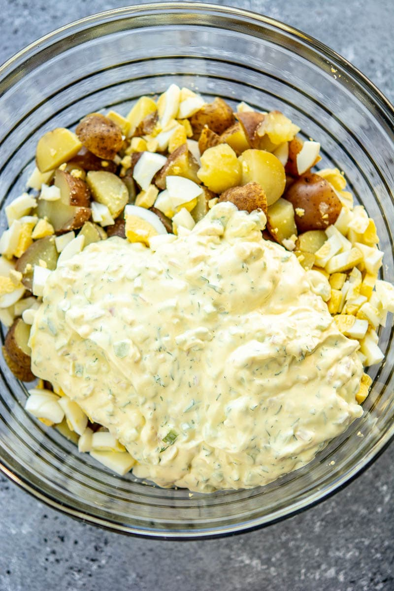 Potato salad ingredients and mayo in a glass bowl