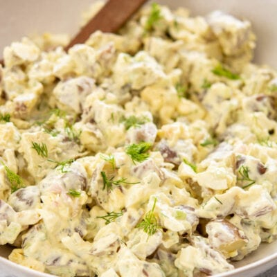 potato salad in a white bowl with a wooden spoon