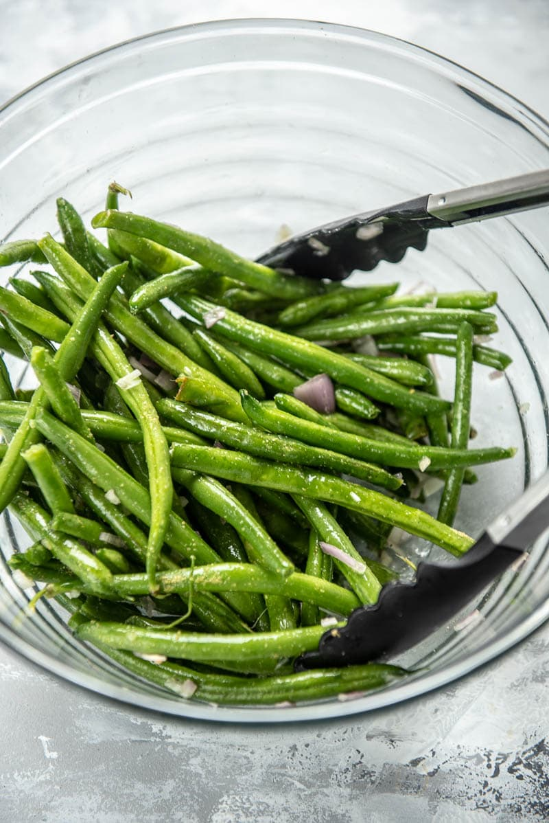 green beans and seasonings in a bowl with tongs