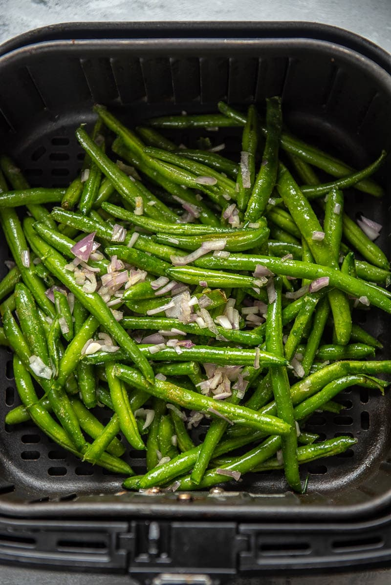green beans and seasonings in air fryer basket