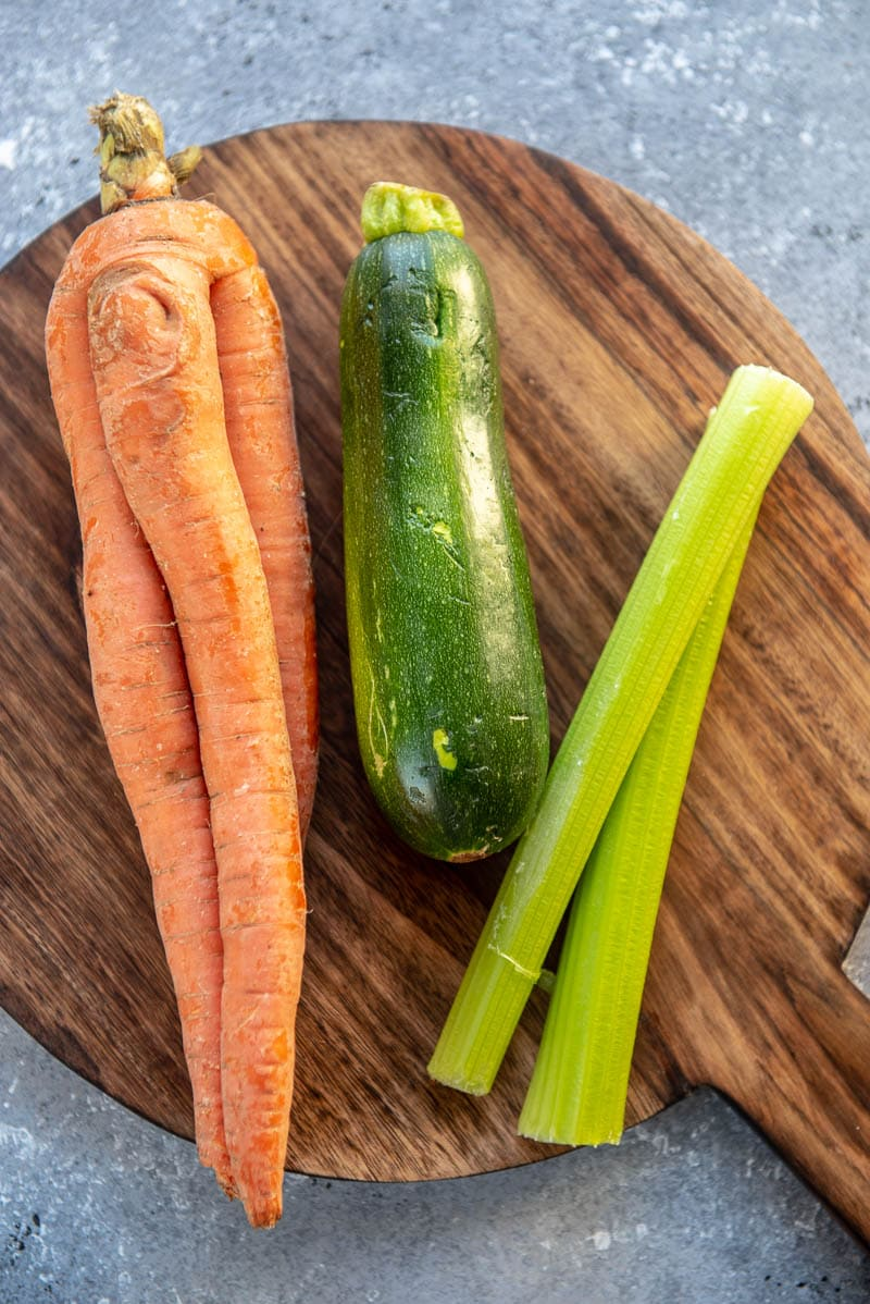 carrot, zucchini, and celery on a cutting board