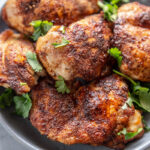 chicken thighs on a plate with garnish