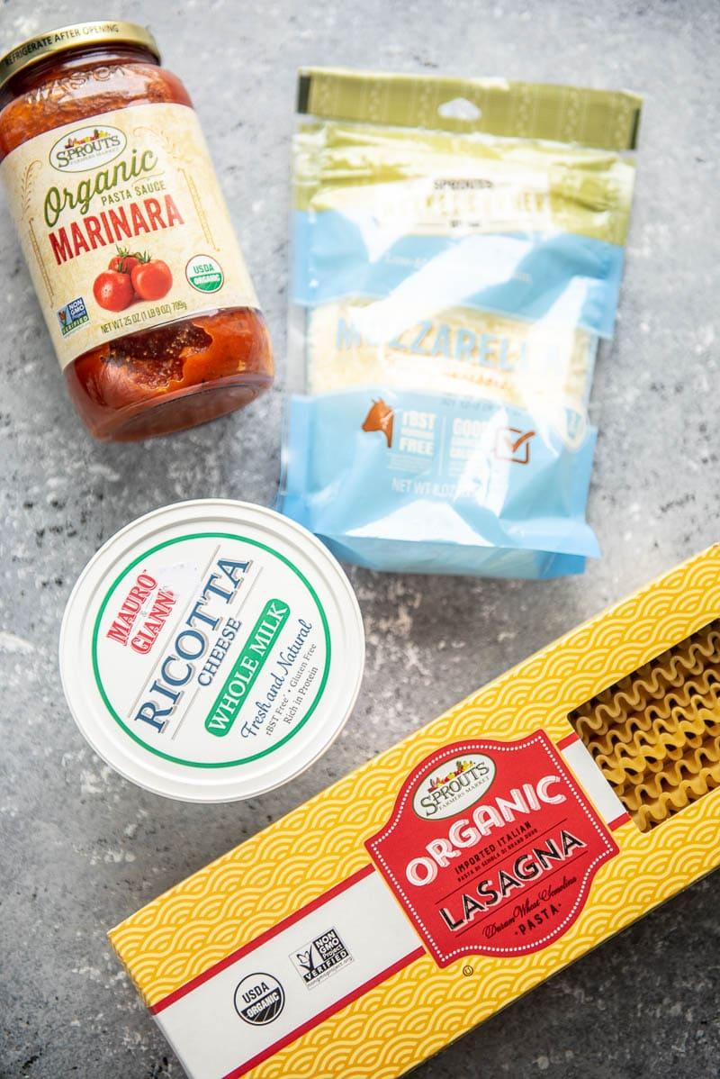 jar of marinara, bag of mozzarella, container of ricotta and box of lasagna noodles