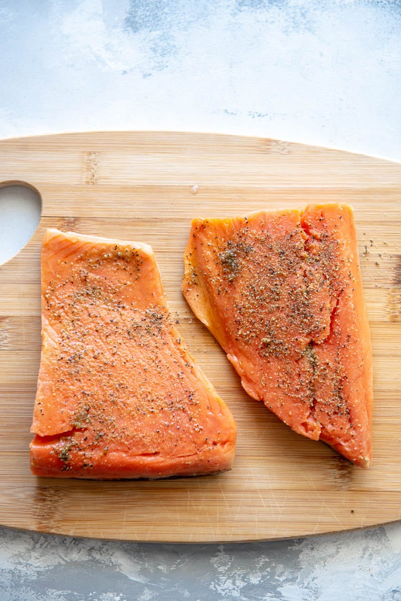 two pieces of salmon on a wood plank