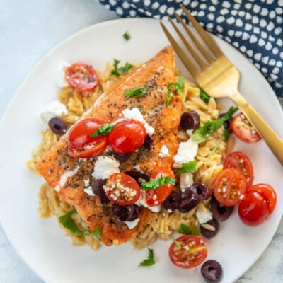 greek salmon on a white plate with fork