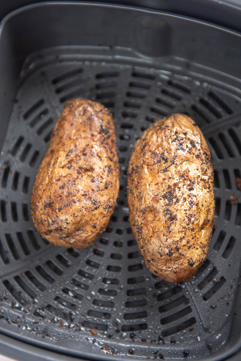 two baked potatoes in an air fryer basket