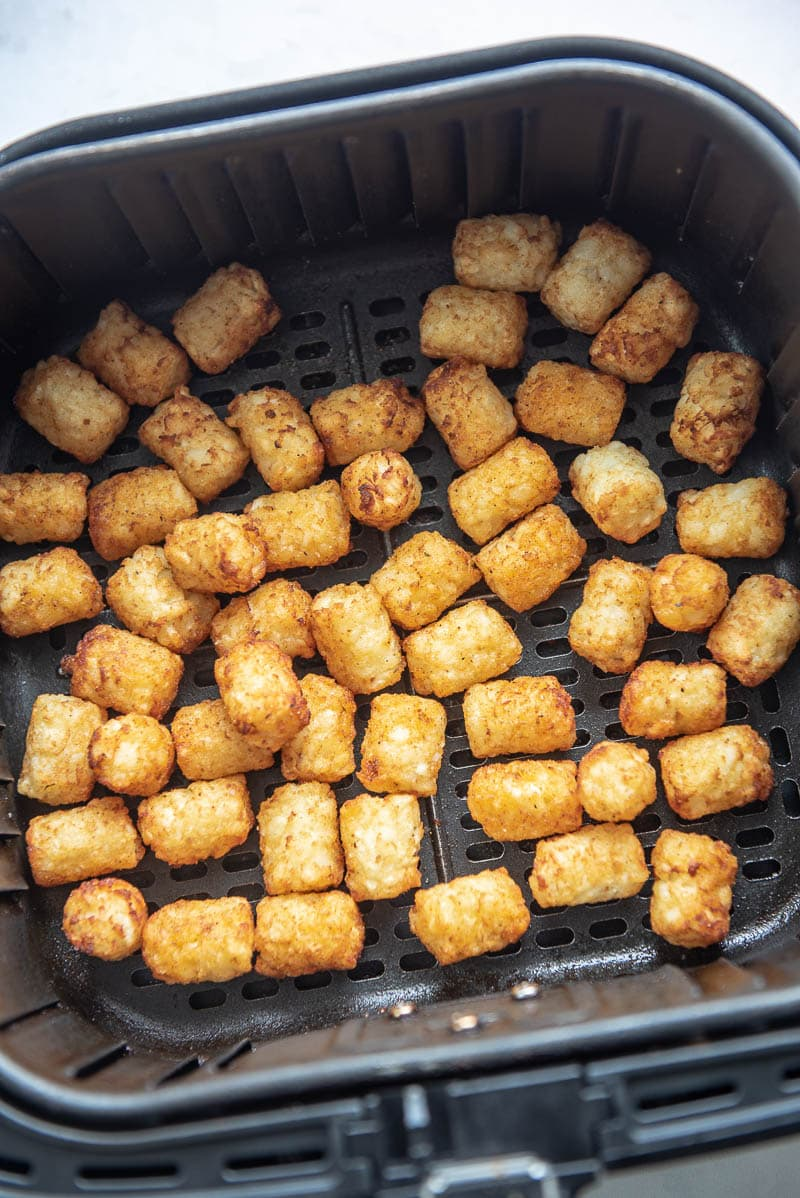 cooked tater tots in an air fryer basket