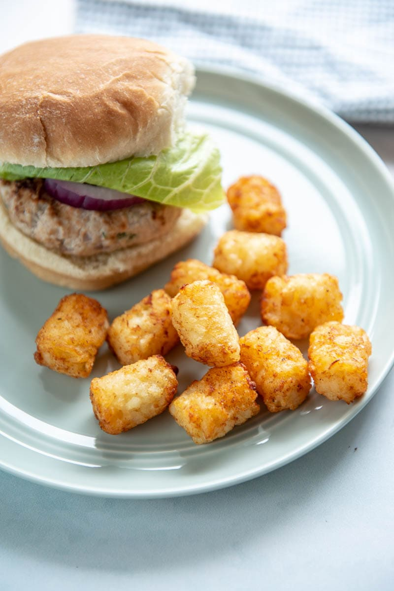 tater tots and a hamburger on a white plate