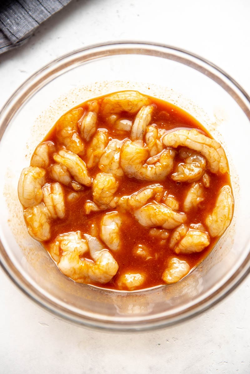 raw shrimp marinating in sriracha sauce and spices