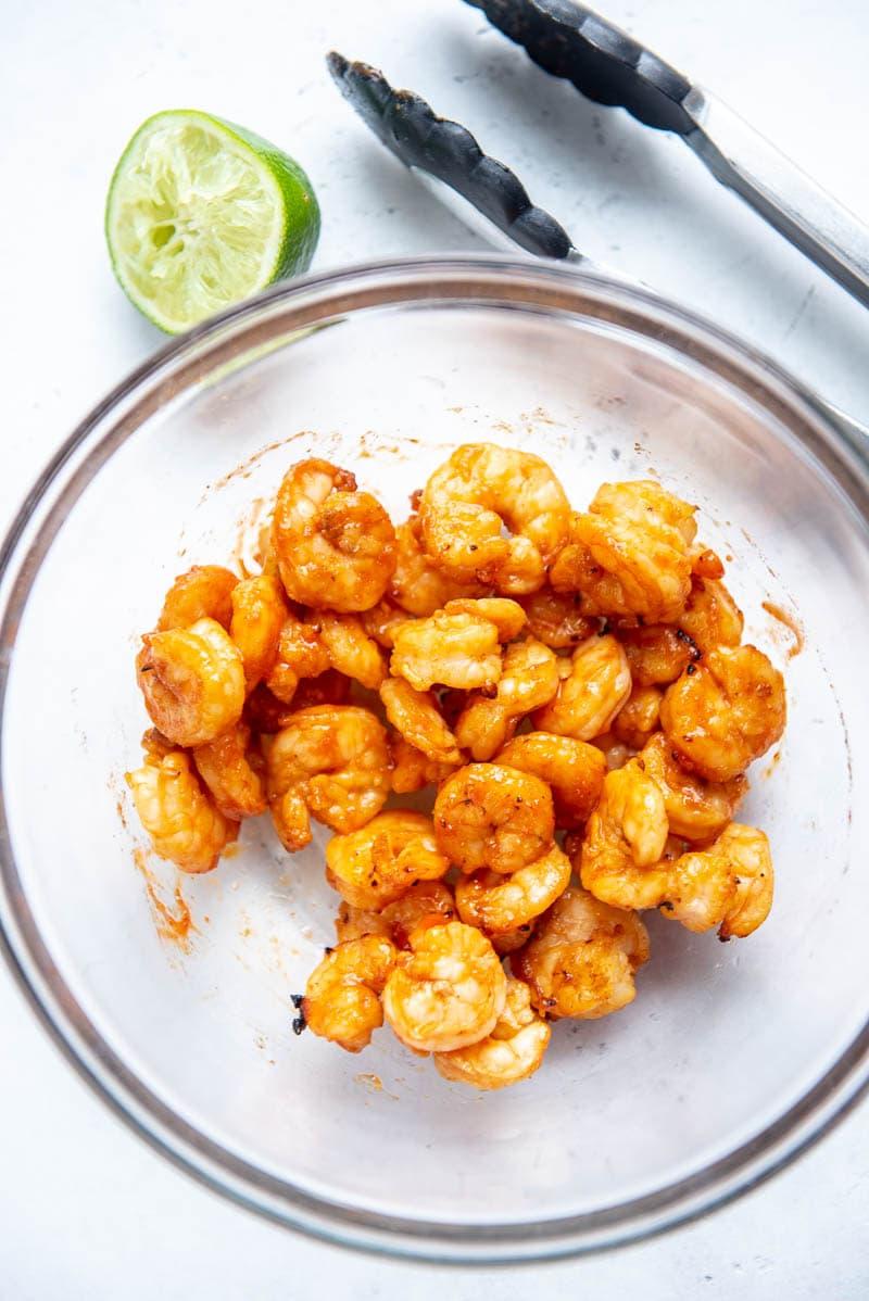 sriracha shrimp on a plate with garnish