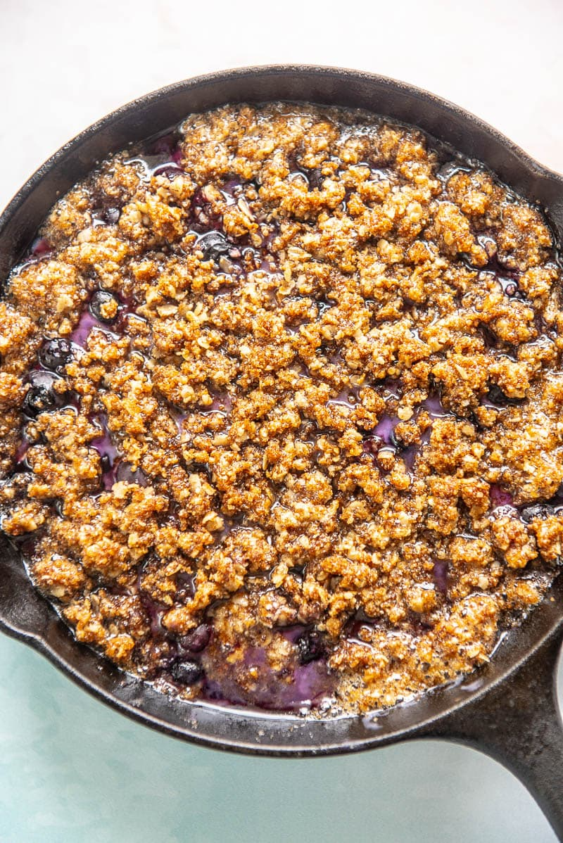 closeup of blueberry crumble in a cast iron skillet