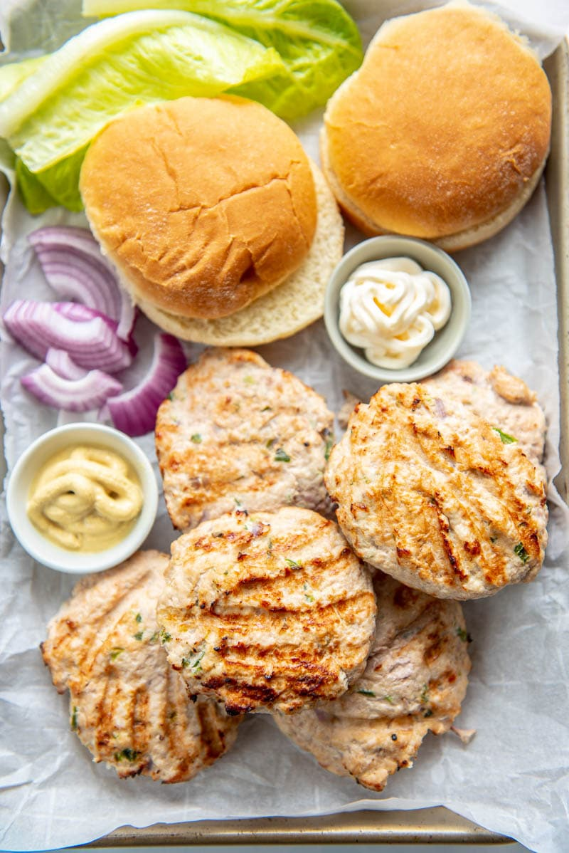 turkey burgers, condiments, and buns on a tray