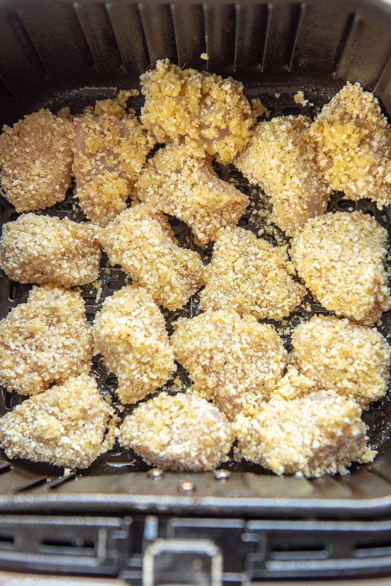 raw chicken nuggets breaded in air fryer basket