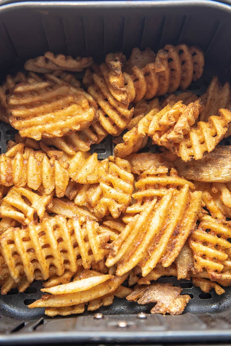 cooked waffle fries in an air fryer basket