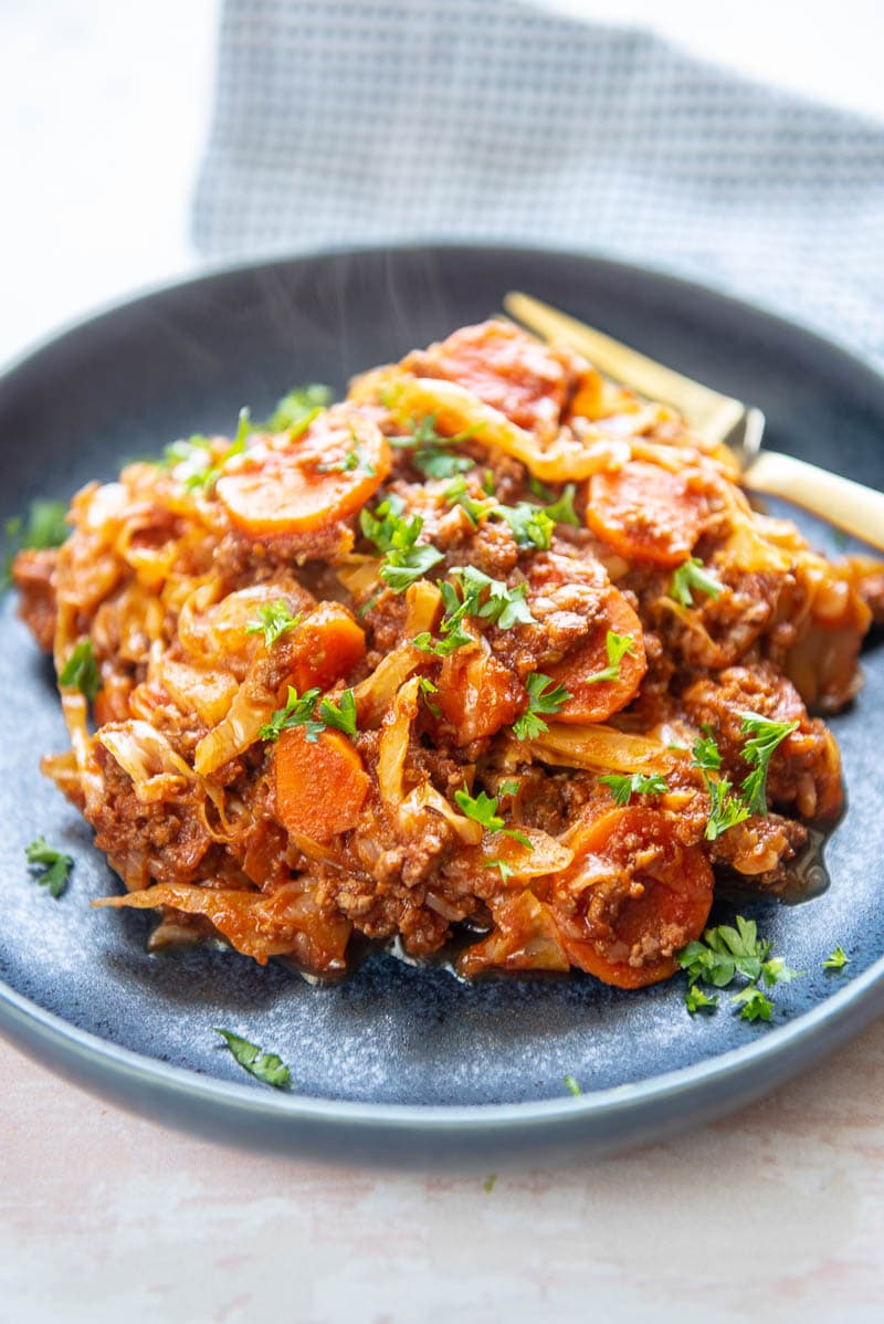 beef and cabbage casserole with carrots on blue plate