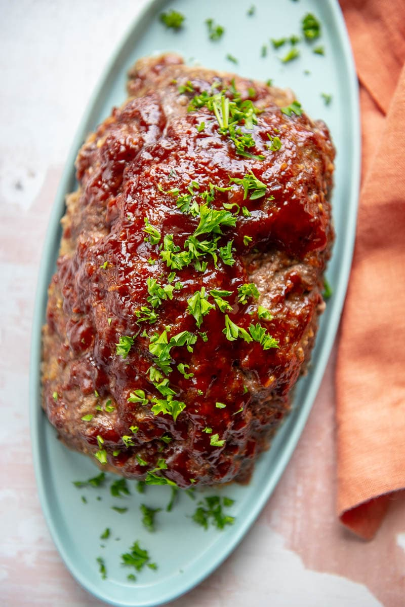 gluten free meatloaf on a blue platter sprinkled with parsley