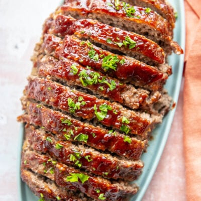 meatloaf sliced on blue platter and topped with sauce and parsley