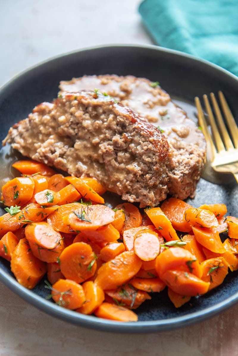 two slices of meatloaf on blue plate with side of sliced carrots