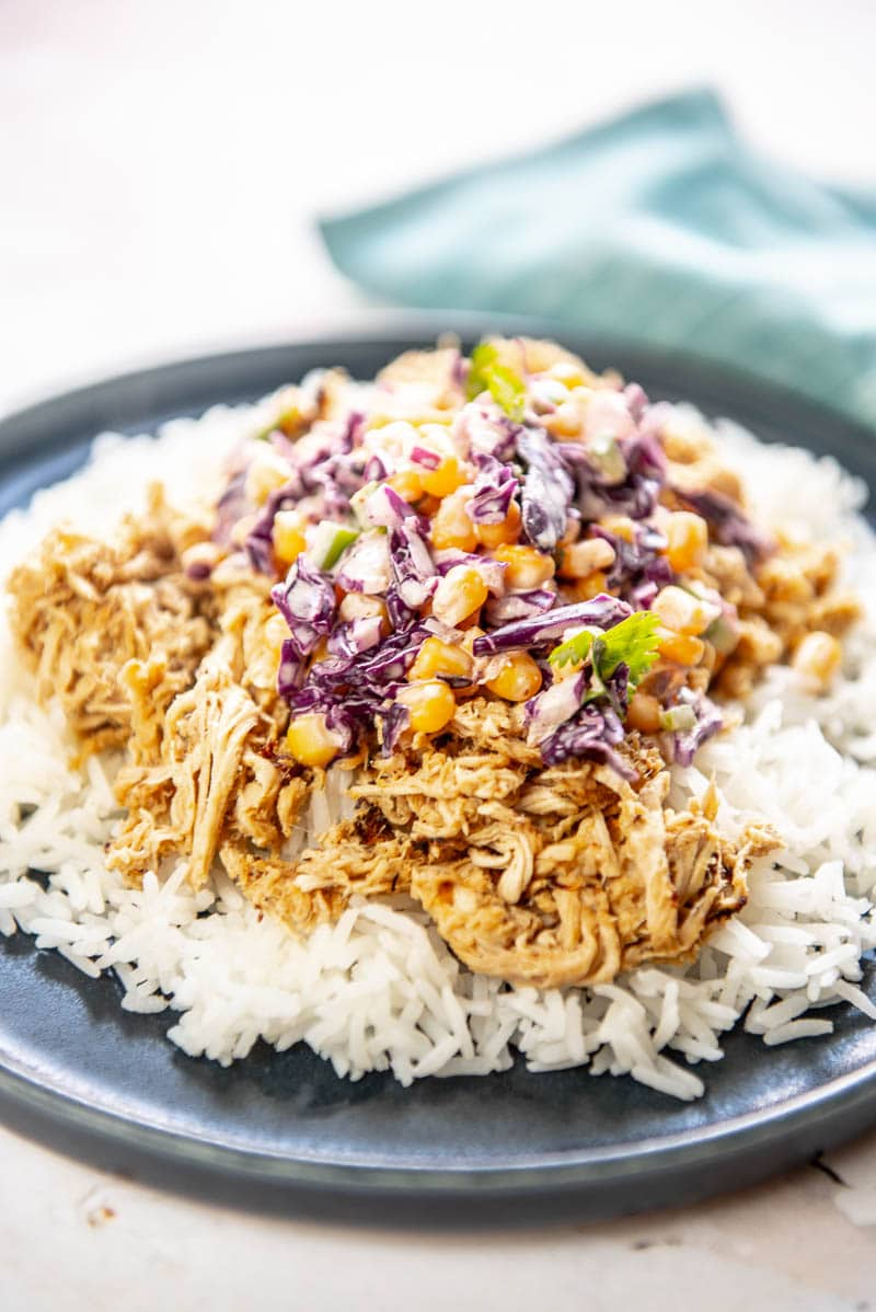 chicken carnitas with corn slaw on rice on a blue plate