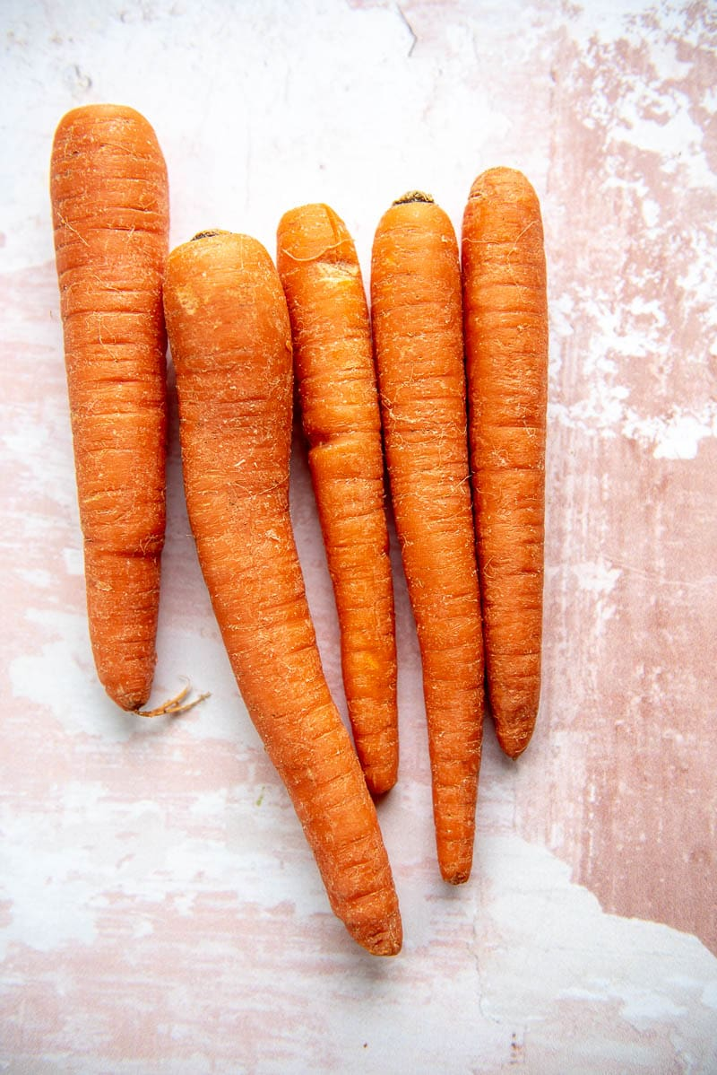 5 carrots on a pink and white table