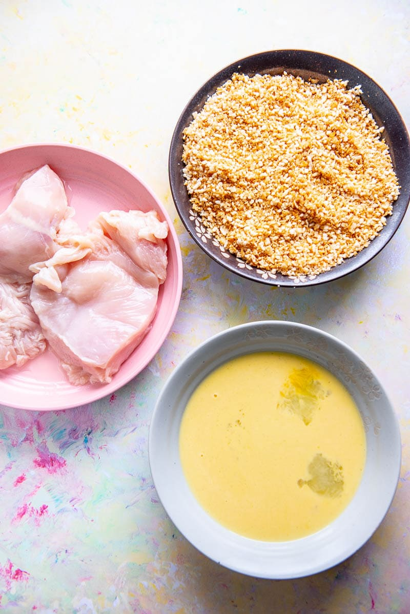 3 bowls one with chicken, one with egg mixture and one with breadcrumbs