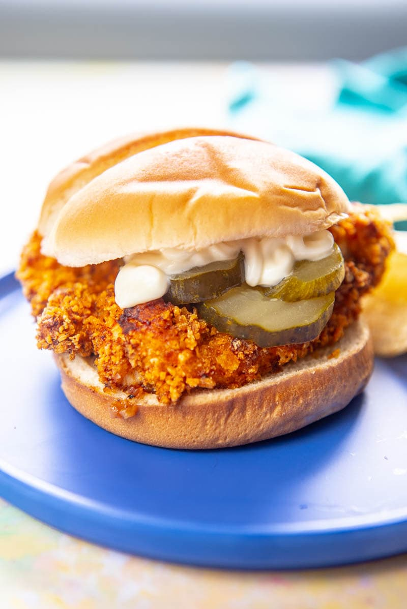 breaded chicken sandwich with pickles and mayo on a blue plate