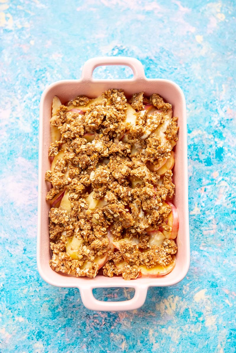 pink casserole dish with peach cobbler ingredients layered and ready to cook
