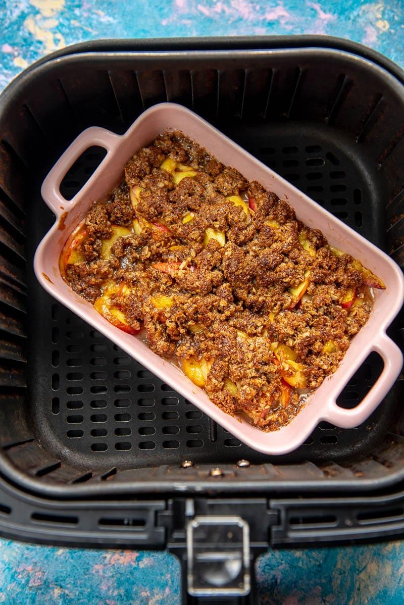 pink casserole dish with peach cobbler in air fryer basket