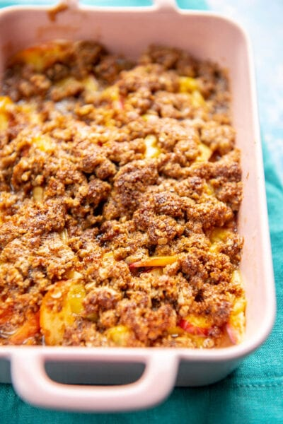 small pink casserole dish with peach cobbler